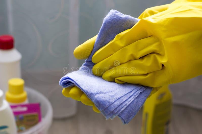 黄色手套的一个女孩拿着一块旧布,特写镜头家事 免版税图库摄影