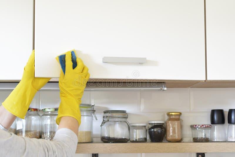 黄色手套的妇女洗涤在厨柜的门 库存图片