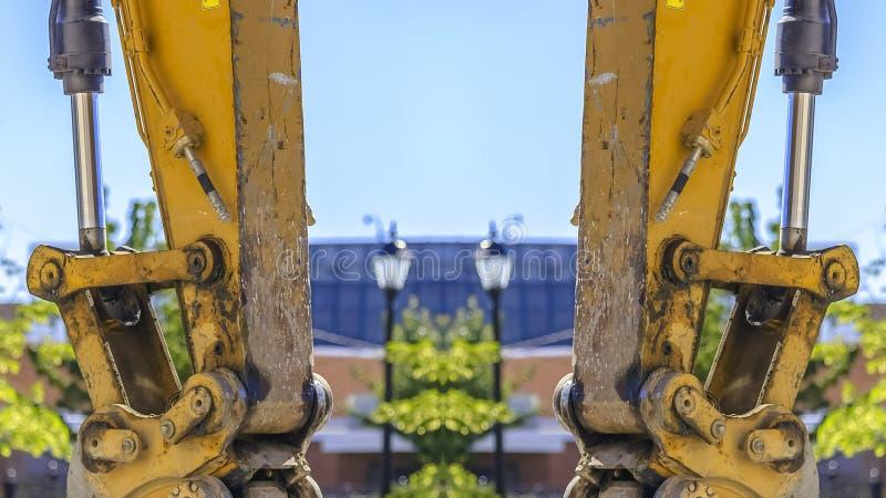 黄色拖拉机胳膊垂直的全景双重视图 皇族释放例证