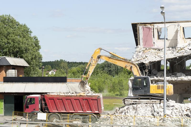 黄色挖掘机装载建筑废料入卡车 技术毁坏大厦,是配件、混凝土和石头 免版税库存照片