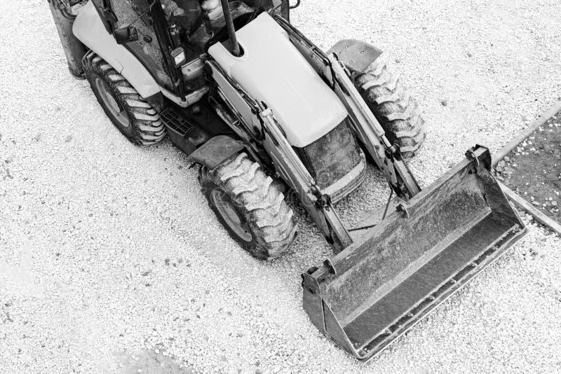 黄色推土机,修路的装载的石渣 黑色白色 免版税库存照片