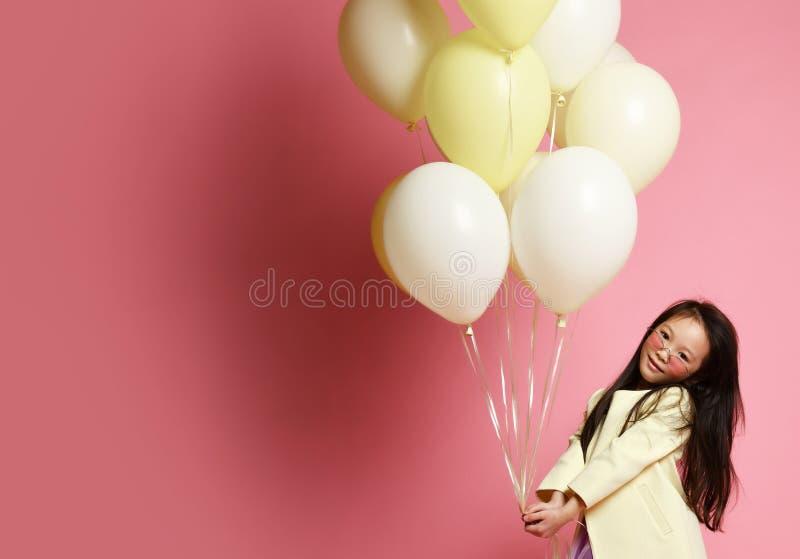黄色时尚夹克的小亚裔女婴和有气球的紫色礼服庆祝愉快微笑 免版税库存图片