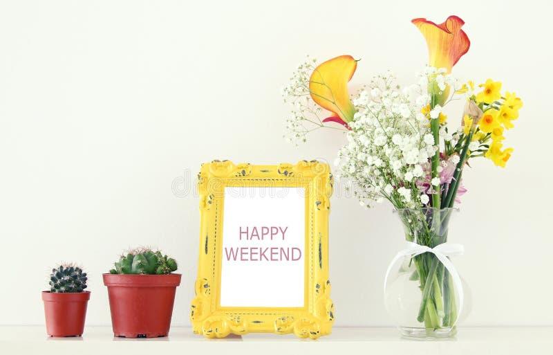 黄色春天美丽的花束的图象在葡萄酒在白色桌的照片框架旁边开花 免版税图库摄影
