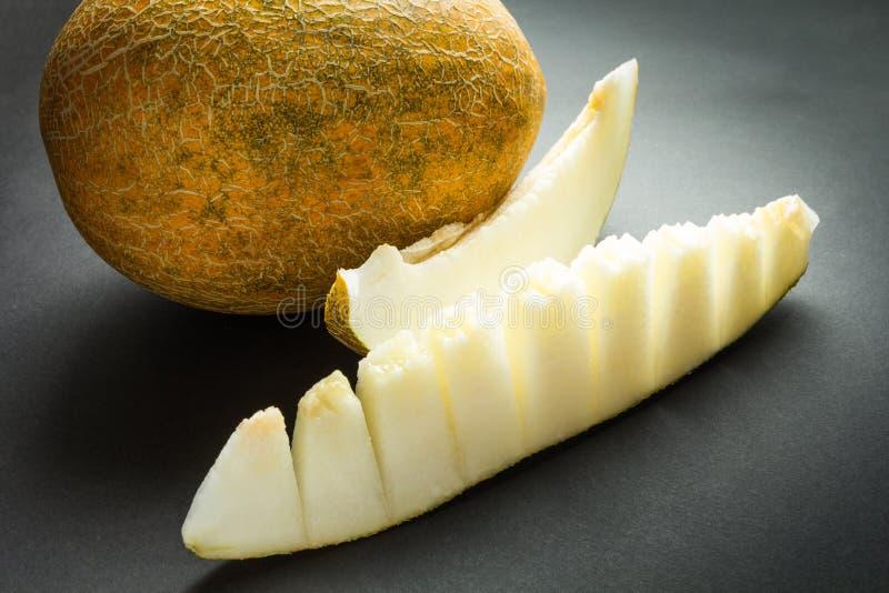 黄色有机在黑色隔绝的甜瓜瓜和切片 免版税库存照片