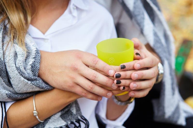 黄色杯子热的茶在恋人的手上 夫妇年轻人 库存图片