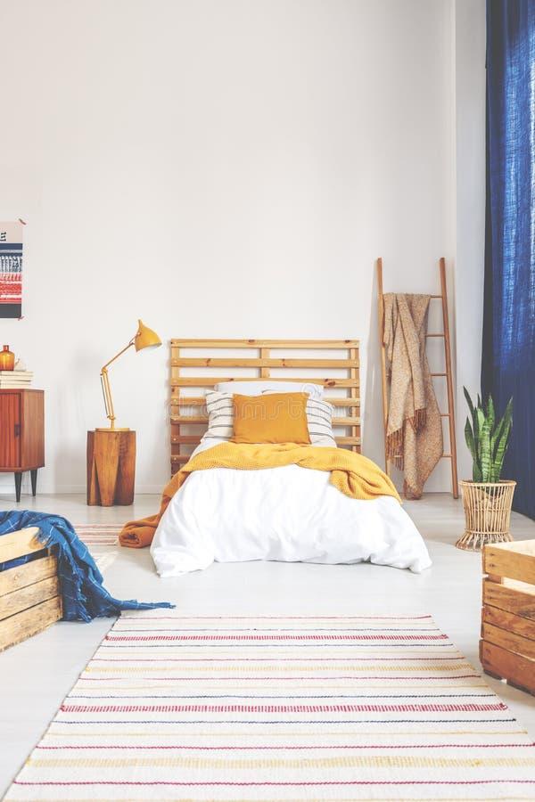 黄色枕头和毯子在舒适的白色木床上在少年卧室有被剥离的地毯的在地板上 免版税库存照片