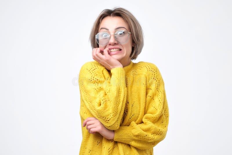 黄色毛线衣的困惑的妇女,保留在面颊的手,看充满恐惧,知道坏消息 免版税库存图片