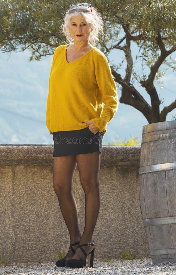 黄色毛衣、黑色迷你裙和网袜的迷人微笑女人肖像 图库摄影