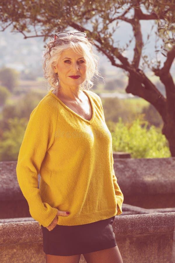 黄色毛衣、黑色迷你裙和网袜的迷人微笑女人肖像 库存图片