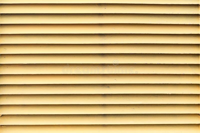 黄色水平的金属窗帘,抽象背景,特写镜头 库存图片