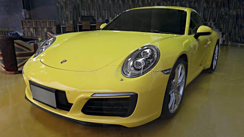 黄色汽车保时捷911 Carrera S在陈列室里 库存图片