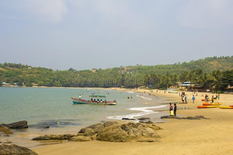 黄色沙滩的人们在有绿色棕榈树和餐馆的蓝色海 库存图片
