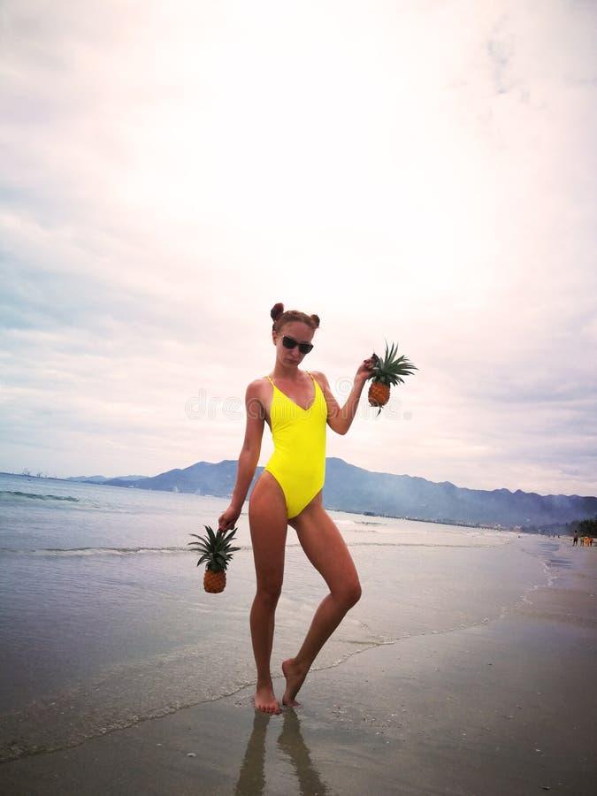 黄色泳装的一个女孩在太阳镜在芽庄市越南支持海 菠萝在手中 免版税库存图片