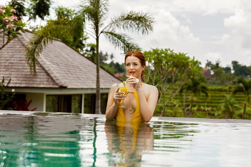 黄色泳装的可爱的女孩在游泳场 免版税图库摄影
