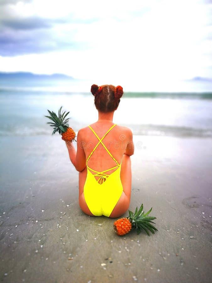 黄色泳装的女孩坐海滩在芽庄市越南 图库摄影