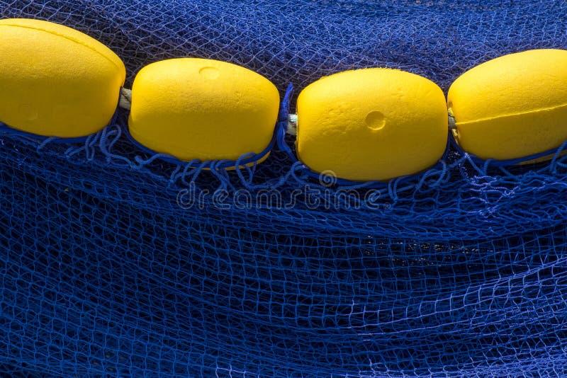 黄色浮游物连续在深刻的蓝色鱼网 图库摄影