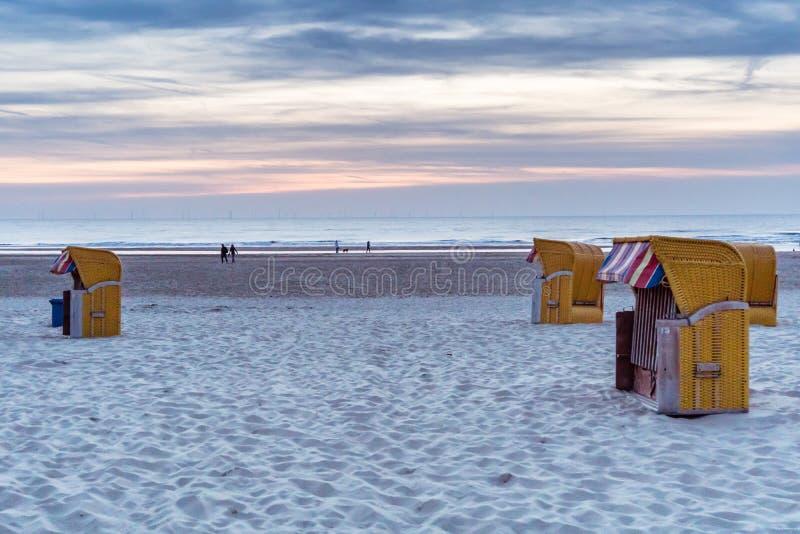 黄色海滩睡椅客舱在一个晚上靠岸 库存照片