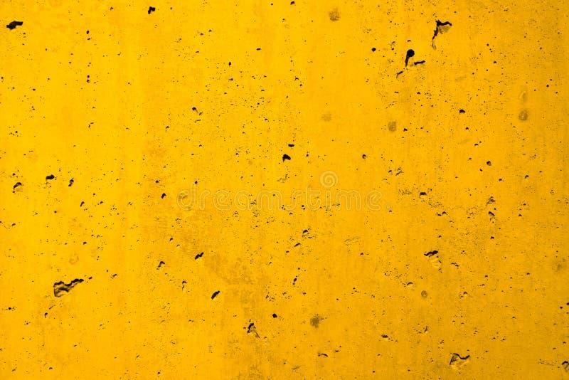 黄色混凝土墙粗糙的门面由自然水泥制成以孔和缺点作为空的土气纹理背景 库存照片
