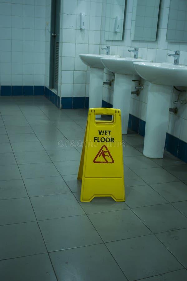 黄色溜滑警报信号,小心湿地板在洗手间屋子签字 免版税库存照片