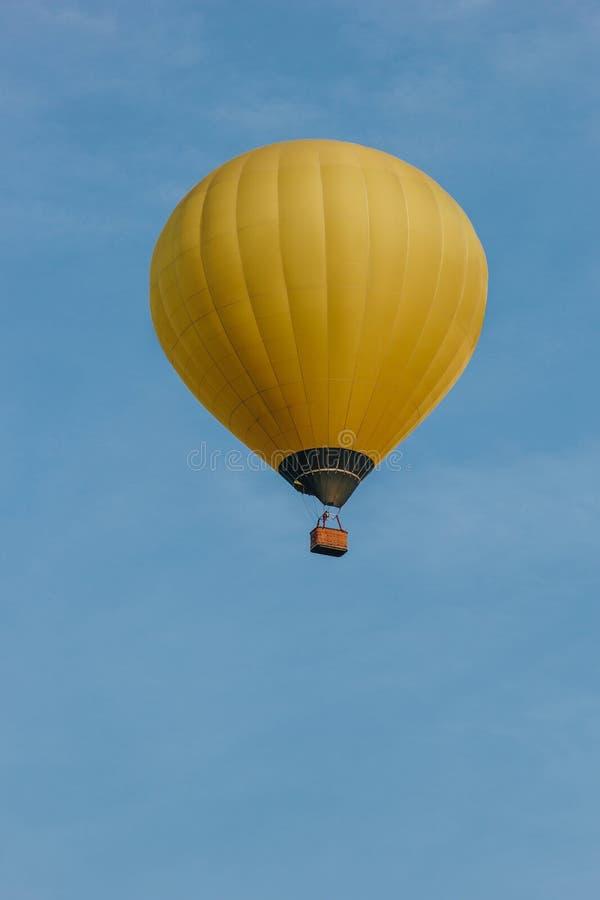 黄色热空气气球飞行底视图  免版税库存照片