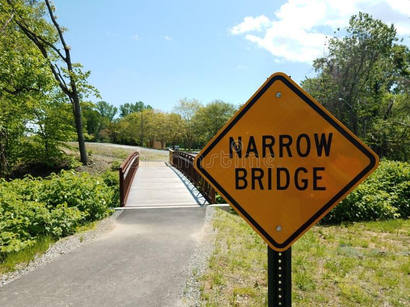 黄色狭窄的桥梁标志和沥青足迹和桥梁 库存照片