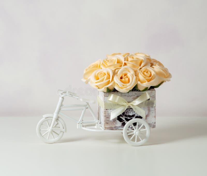 黄色玫瑰花束在一个木小装饰箱子的以在轻的背景的一辆自行车的形式 葡萄酒 免版税库存图片