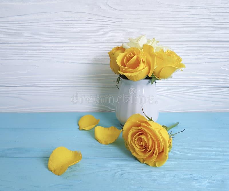 黄色玫瑰花瓶木背景问候装饰 库存照片