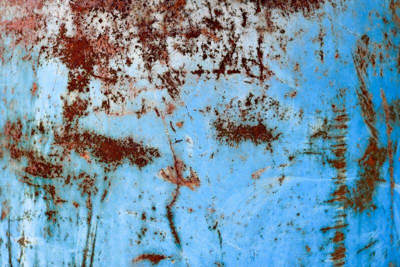 黄色生锈的老破旧的粗糙的生锈的独特的铁锈,被氧化的金属,在蓝色削皮油漆的铁纹理  免版税库存照片