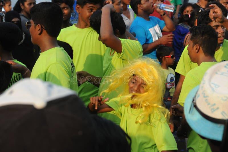 黄色的享用在狂欢节的女孩和人们在果阿,印度 免版税库存照片