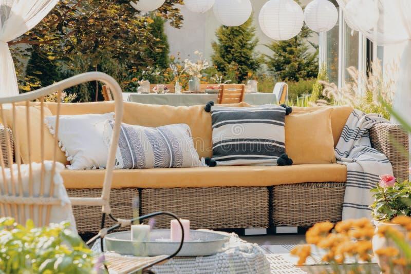 黄色的真正的有桌的照片,沙发和灯在背景中 植物特写镜头  图库摄影