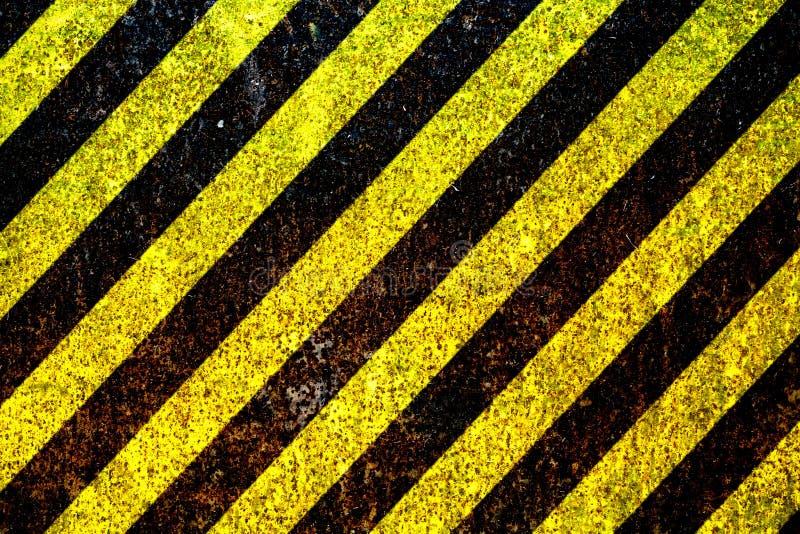 黄色的警报信号和黑条纹被绘在生锈金属片当纹理背景 库存图片