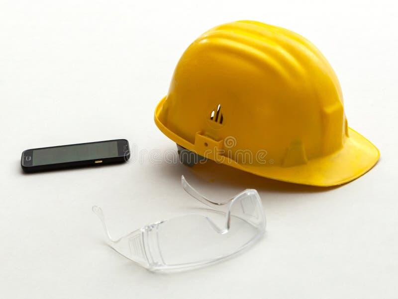 黄色盔甲、防护玻璃和手机 免版税库存照片