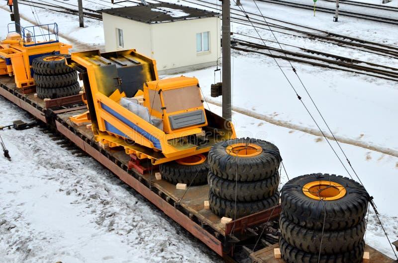 黄色矿用汽车被拆卸入零件,小室,身体,电动机,驱动,轮子,被装载在货物铁路平台上 库存照片