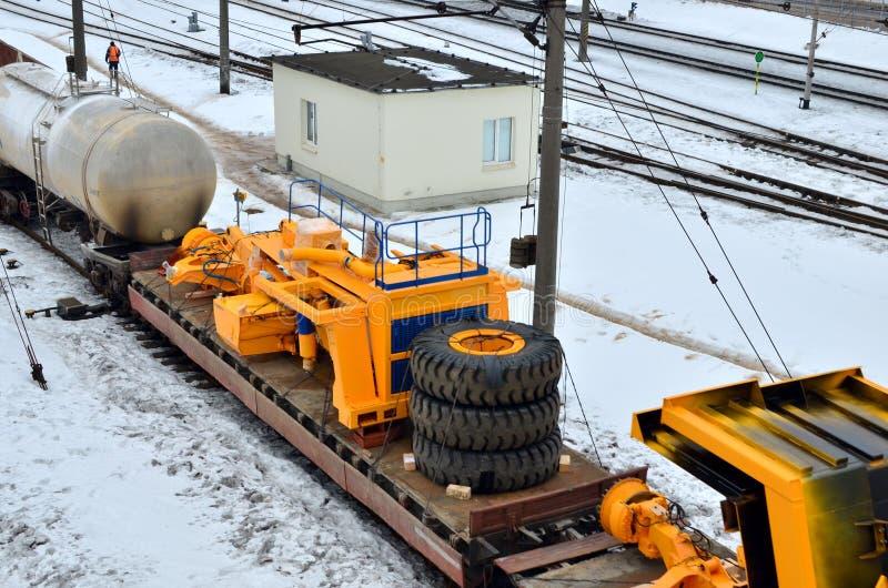 黄色矿用汽车被拆卸入零件,小室,身体,电动机,驱动,轮子,被装载在货物铁路平台上 图库摄影