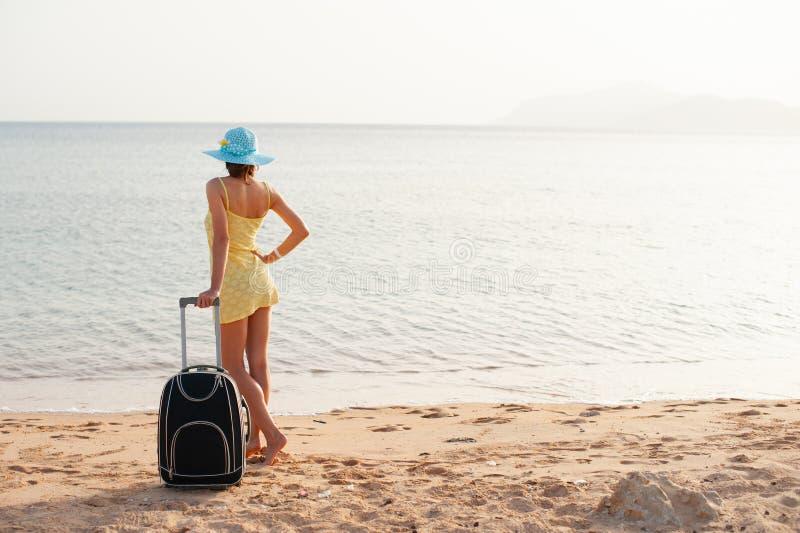 黄色礼服和帽子的年轻美女带着在热带海滩的大手提箱 在海的女孩神色 库存图片
