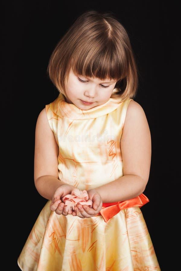 黄色礼服的小白肤金发的女孩拿着桃红色玫瑰 免版税库存图片