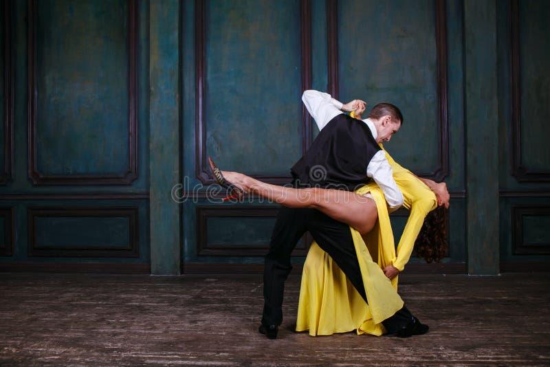 黄色礼服的年轻俏丽的妇女和人跳舞探戈 免版税图库摄影