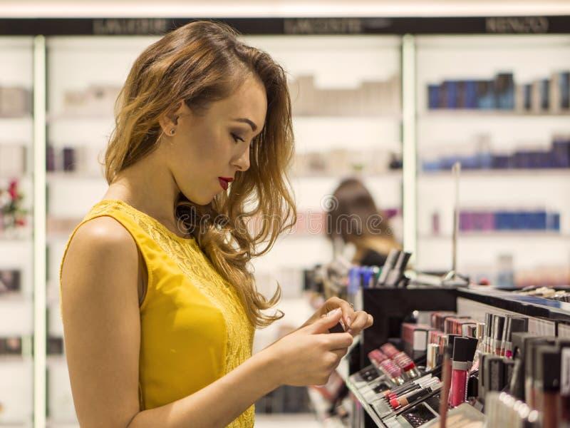 黄色礼服的年轻可爱的微笑的女孩在化妆用品商店选择新的唇膏 图库摄影