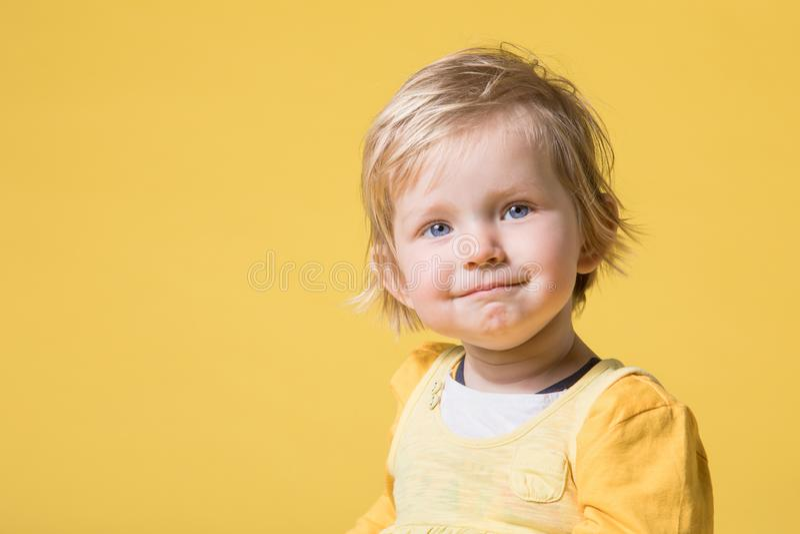 黄色礼服的年轻女婴在黄色背景 库存图片