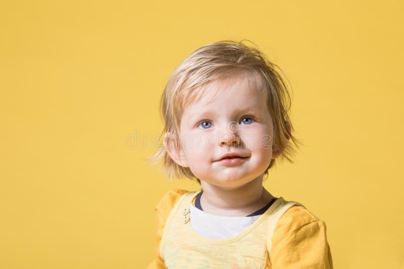 黄色礼服的年轻女婴在黄色背景 免版税库存照片