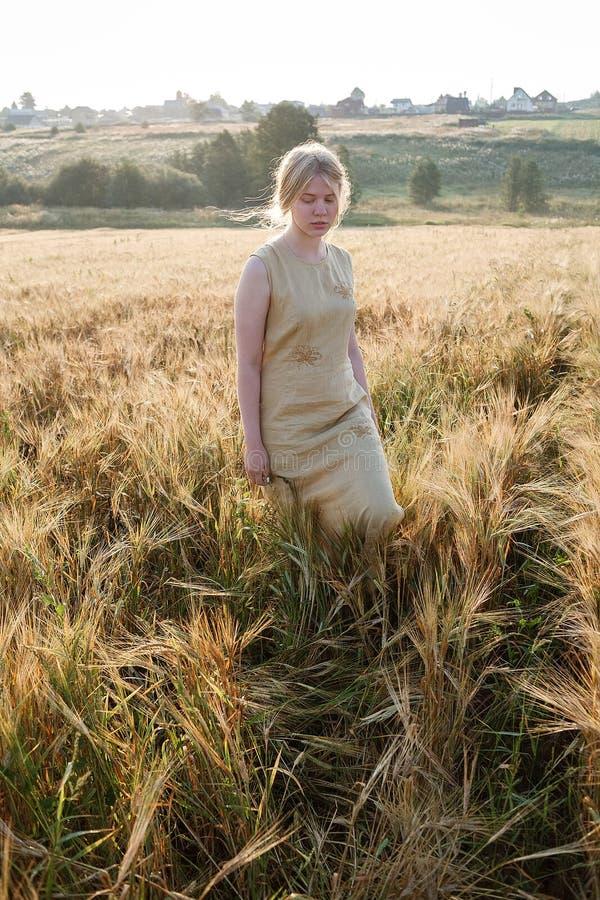 黄色礼服立场的年轻俏丽的女孩在耳朵的领域在朝阳光芒的  树丛和村庄在背景中 库存图片