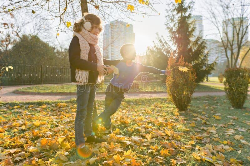 黄色秋天季节、走在公园的孩子男孩和女孩 库存图片