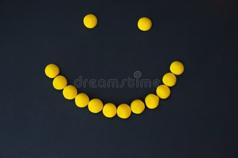 黄色糖果糖衣杏仁微笑在黑背景的 免版税库存照片