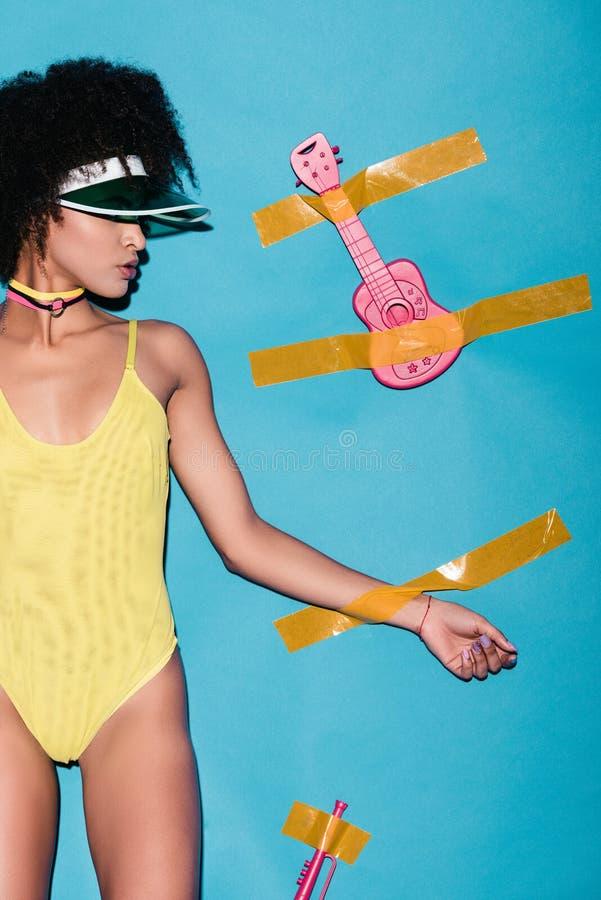 黄色紧身衣裤和桃红色玩具吉他的时髦的非裔美国人的女孩胶合与透明胶带 免版税库存照片