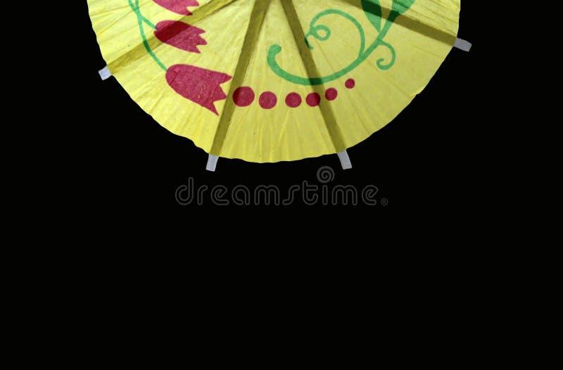 黄色纸鸡尾酒伞东方装饰的细节在黑背景的 库存图片