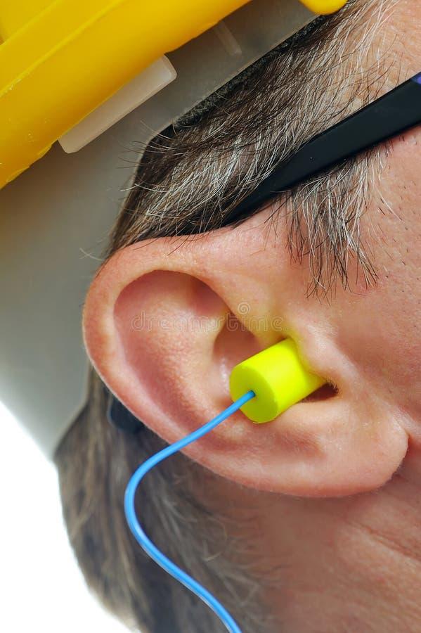 黄色耳塞到耳朵里 库存图片