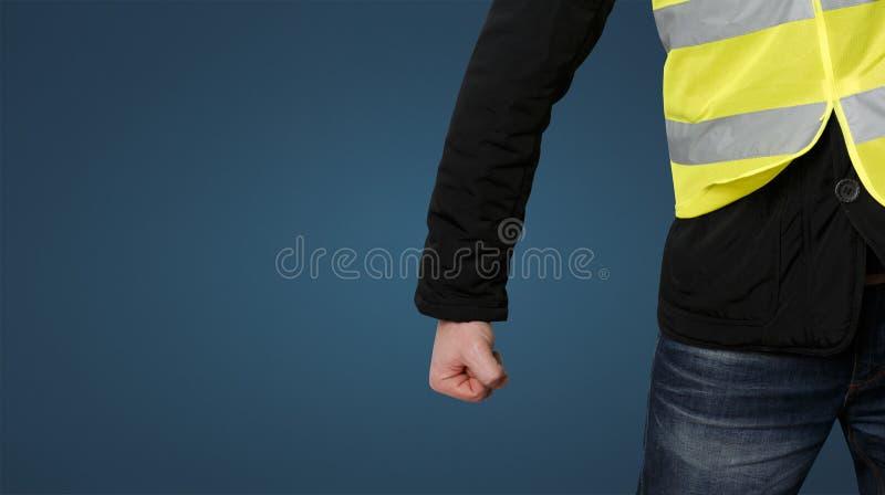 黄色背心抗议 一个无法认出的人握紧了他的在抗议的拳头在蓝色背景 革命和抗议的概念 免版税库存照片