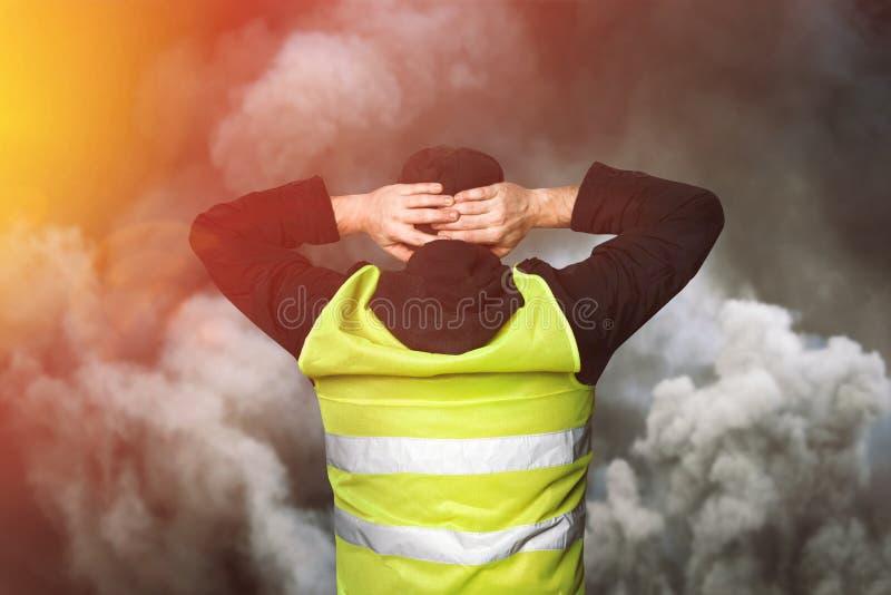 黄色背心抗议 年轻人站立与他的并且握他的在他的头的手作为守纪的标志在催泪弹的 免版税图库摄影