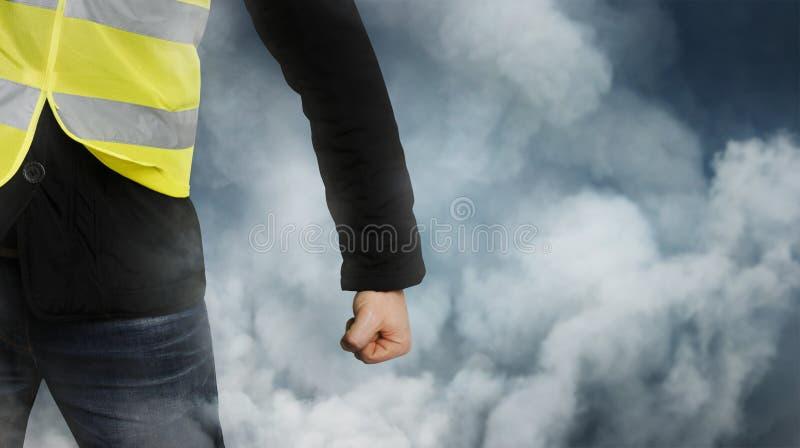黄色背心抗议 无法认出的人握紧了他的在抗议的拳头在阴霾 库存照片