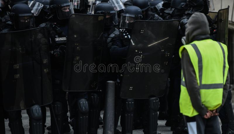 黄色背心- Gilets jaunes抗议-单独站立在防暴警察前面的抗议者 库存图片